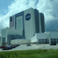 The blue of U.S. flag on the Vehicle Assembly Building is the size of a basketball court and each stripe as wide as a road lane.
