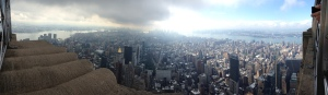 Dramatic panorama from Empire State Building on the same cloudy day with the sky opening up.